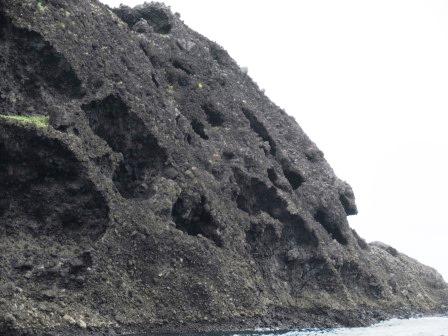 黒い色をした馬島。深海中の火山爆発で出来た破砕岩が隆起した後、塩が固まる時に体積が膨張し破砕岩を崩し、雲形浸食が出来ました。
