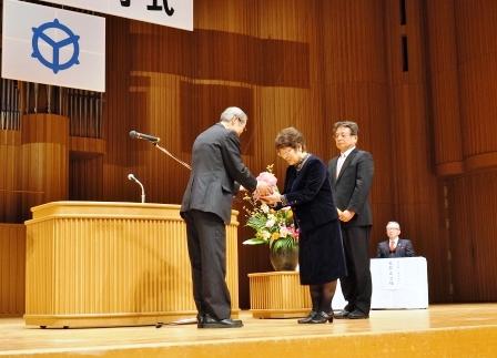 皆勤賞49人の代表として賞状と花を受取る早戸澄男さんと渡辺定子さん
