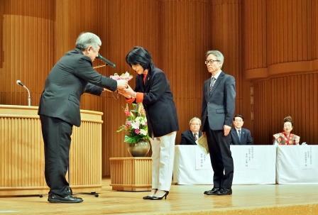 皆勤賞60人の代表として賞状と花を受取る堂原克行さんと桑原都子さん